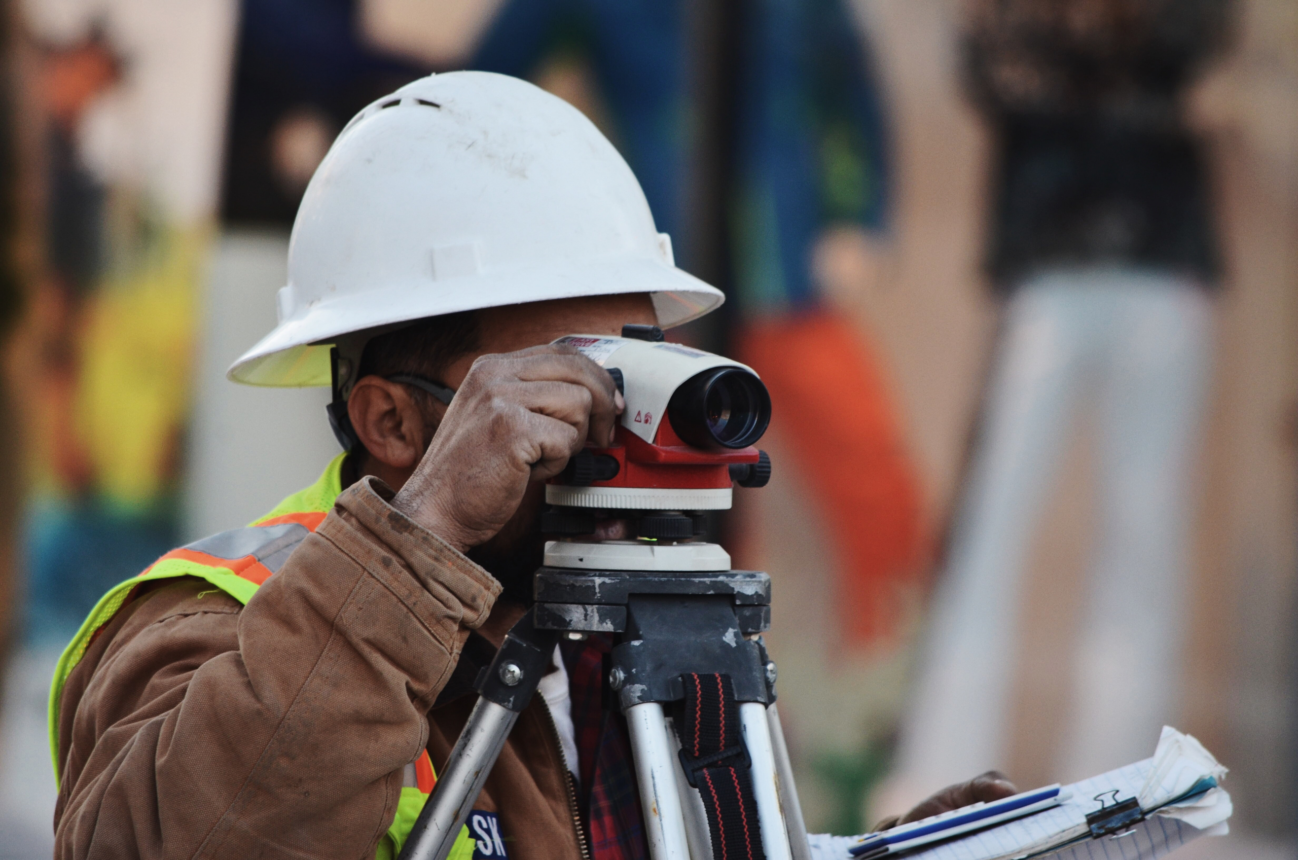 Man wearing a hard hat using a surveying device
