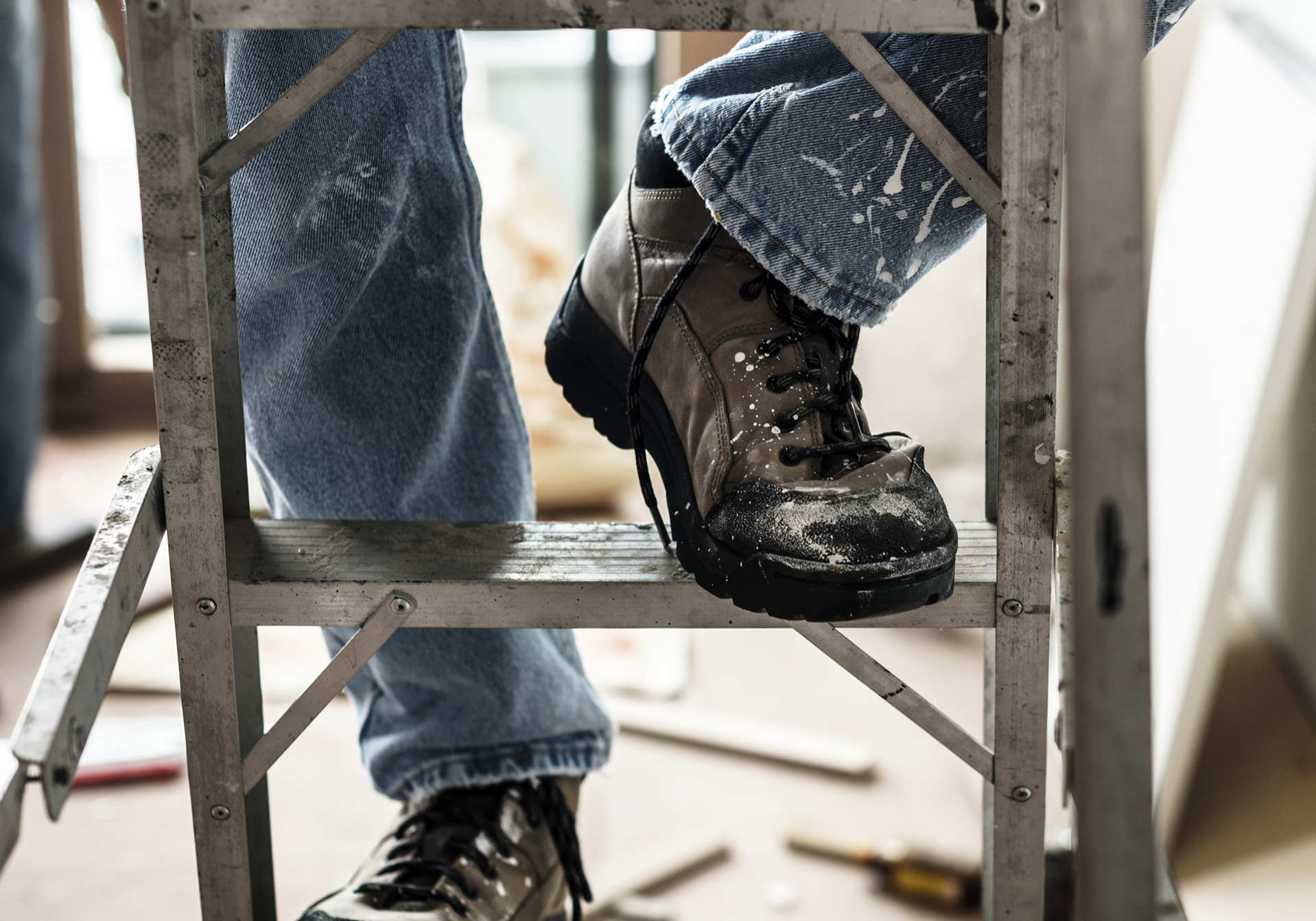 Construction worker stepping on ladder